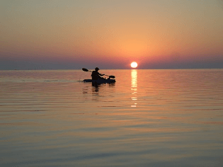 Single kayak sunset on gulf
